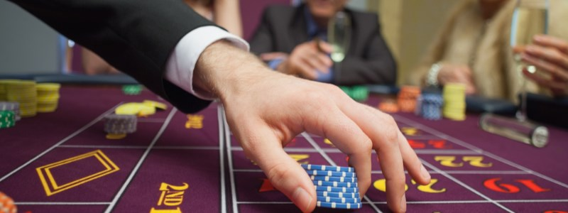 Man playing roulette chips on table