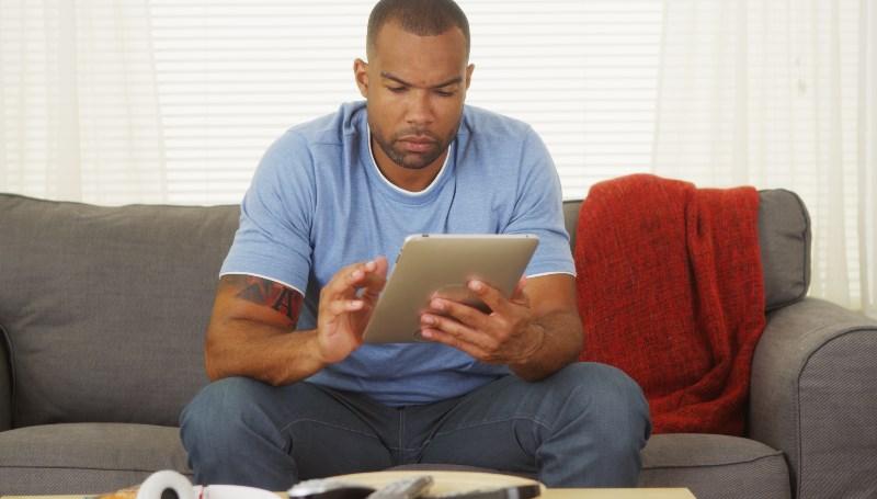 Man gambling on tablet from kenya